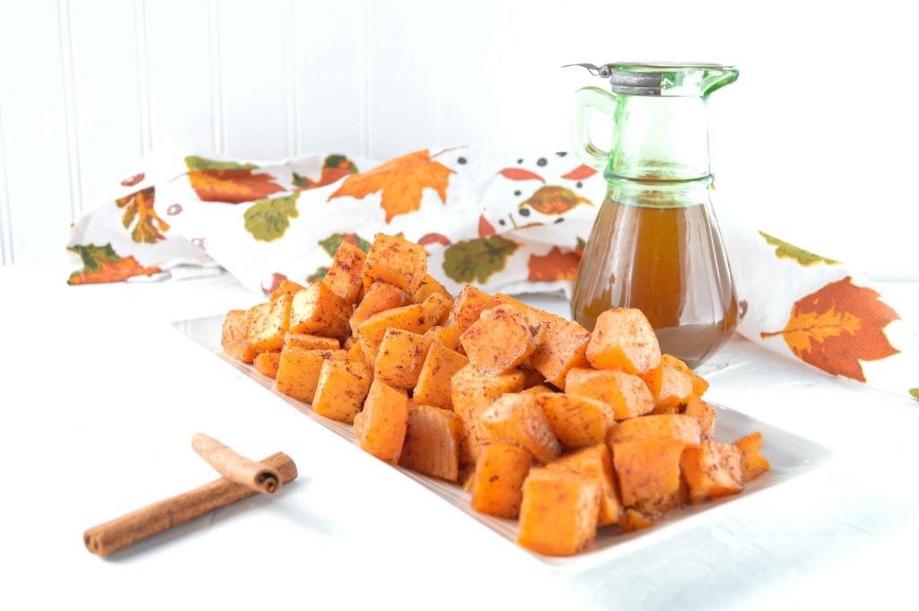 Candied Butternut Squash on a white rectangle plate with two cinnamon sticks to the right. There is a green jar of Maple Syrup a towel with a fall leaves behind it. www.atwistedplate.com