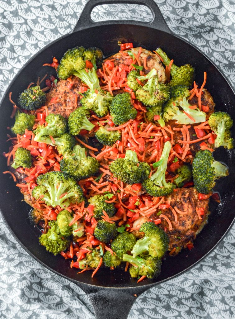 Top view of a cast iron skillet with chicken, broccoli, carrots, and red peppers. Cast iron is sitting on a teal and white towel. www.atwistedplate.com
