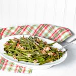 "Pinterest Image for Perfectly Roasted Potatoes. Top picture is Bacon Green Beans in a white oval bowl with a silver spoon sticking out on the right hand side. The background is white with a red/white and green plaid towel. Below in white letters with a green background it says ""Bacon Green Beans"". Below is a close up side view Bacon Green Beans in a white oval bowl with a silver spoon sticking out on the right hand side. The background is white with a red/white and green plaid towel. www.atwistedplate.com"