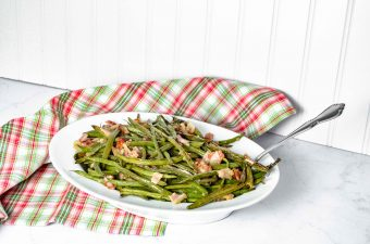 """Pinterest Image for Perfectly Roasted Potatoes. Top picture is Bacon Green Beans in a white oval bowl with a silver spoon sticking out on the right hand side. The background is white with a red/white and green plaid towel. Below in white letters with a green background it says """"Bacon Green Beans"""". Below is a close up side view Bacon Green Beans in a white oval bowl with a silver spoon sticking out on the right hand side. The background is white with a red/white and green plaid towel. www.atwistedplate.com"""