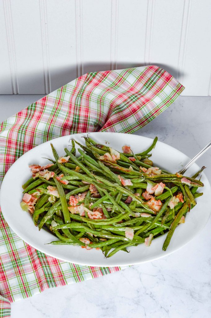 Bacon Green Beans in a white oval bowl with a silver spoon sticking out on the right hand side.  The background is white with a red/white and green plaid towel. www.atwistedplate.com