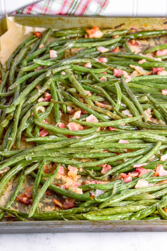 Bacon Green Beans on a metal baking sheet with parchmaent paper. The background at the top is white with a red/white and green plaid towel. www.atwistedplate.com
