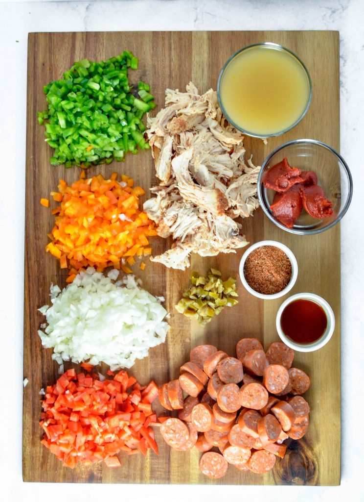 Ingredients for Cajan Chicken, Sausage and Peppers on a wood cutting board. www.atwistedplate.com