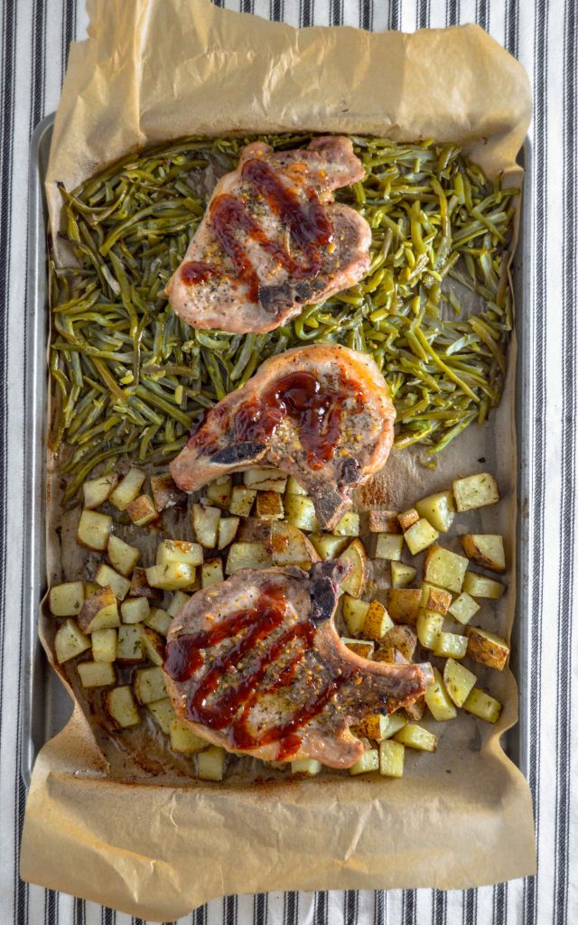 Vertical sheet pan with parchment paper.  on the bottom half is cubed potatoes, on the top half is green beans.  On top are three pork chops with BBQ Sauce on it.Sheet Pan Pork Chop Dinner. www.atwistedplate.com