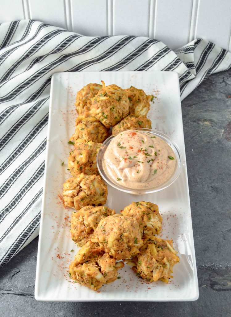 Image is a top angle view of Paleo Maryland Crab Ball on a white rectangle plate.  There is a bow of Old Bay Aioli on the plate.  The plate is on a gray background with a black and white dish towel on the left.   www.atwistedplate.com