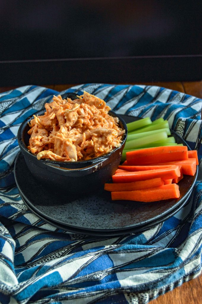 Side, slight angle view of Buffalo Chicken Dip in a black bowl on a black plate with celery and carrots.  Plate is sitting on a blue and white triangle towel against a dark background.  www.atwistedplate.com
