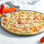 Side angled image of vegetable pizza against a white background with red, yellow and orange peppers. www.atwistedplate.com