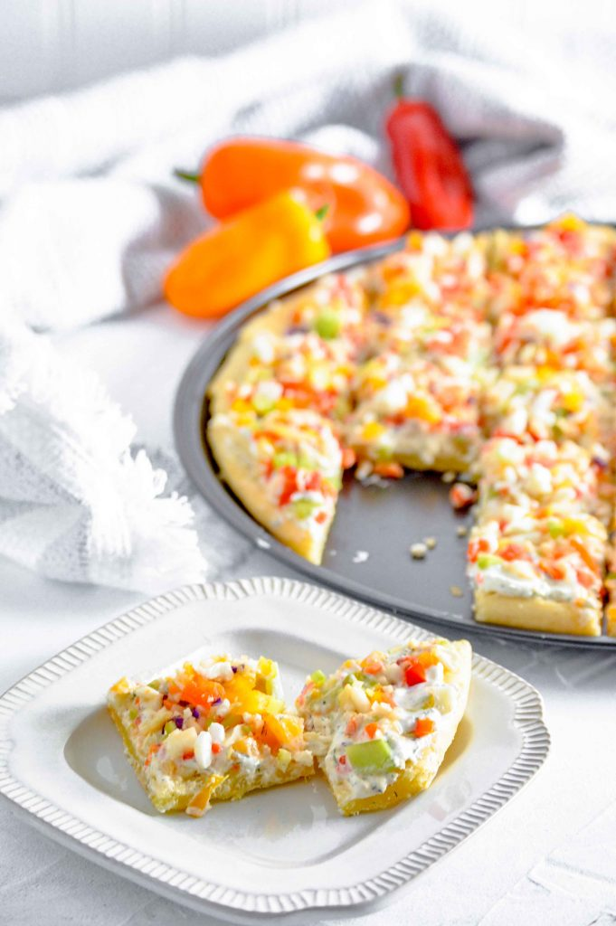 Side angled view of half a cut up vegetable pizza against a white background with red, yellow and orange peppers, and a silver pizza cutter. There are two pieces cut out on a white plate in-front of it. https://www.atwistedplate.com/veggie-pizza/