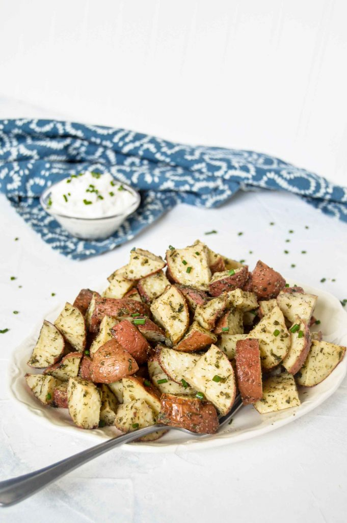 Angled view of Roasted Ranch Potatoes on a white plate. In the top right corner is a blue and white towel with a bowl of sour cream with chives. https://www.atwistedplate.com/roasted-ranch-potatoes/