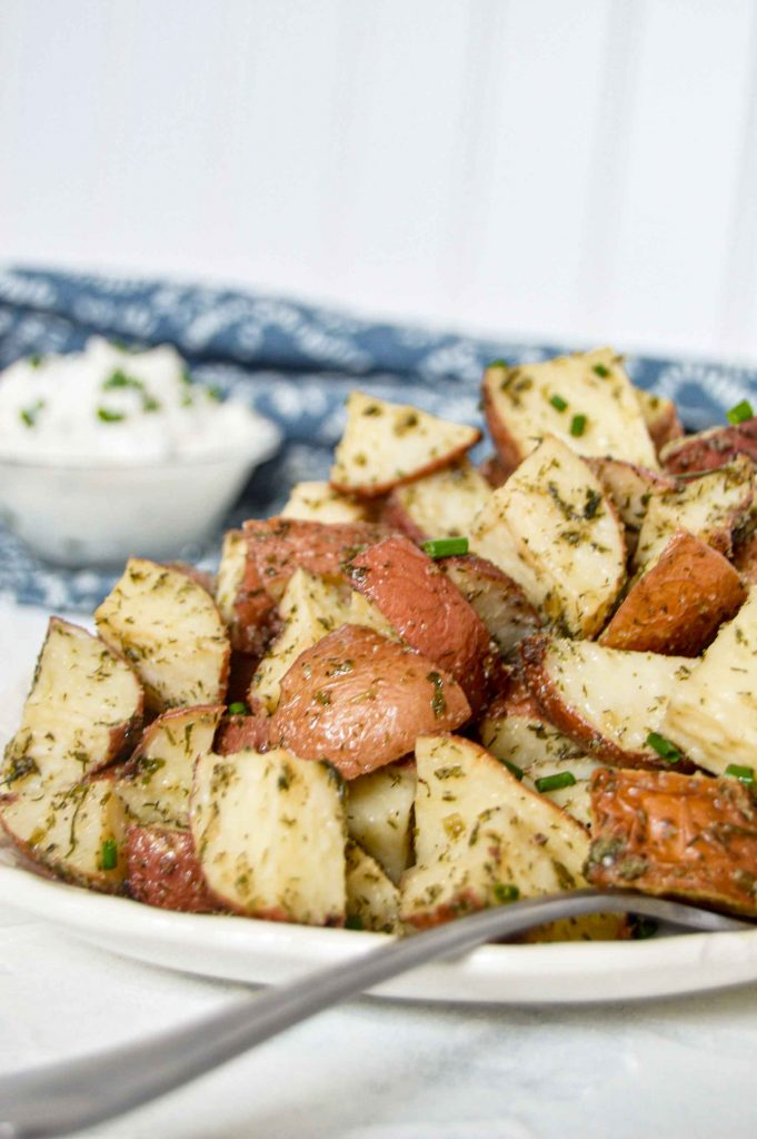 Side close up of have a plate of Roasted Ranch Potatoes on a white plate. In the top right corner, blurred, is a blue and white towel with a bowl of sour cream with chives. https://www.atwistedplate.com/roasted-ranch-potatoes/