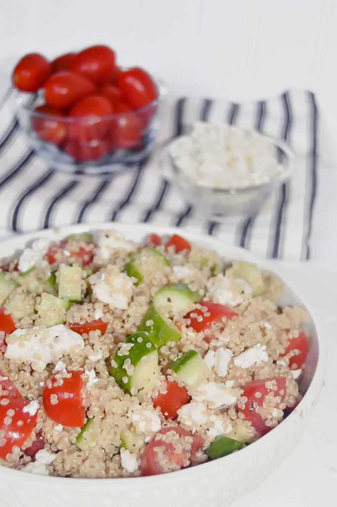 Quinoa Salad with Cucumber, Tomato and Feta with a bowl of tomatoes and a bowl of feta on a black and white towel. www.atwistedplate.com