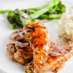 Closeup image is a closeup of Maple Balsamic Glazed Chicken on a white plate with broccolini behind it. https://www.atwistedplate.com/maple-balsamic-glazed-chicken/