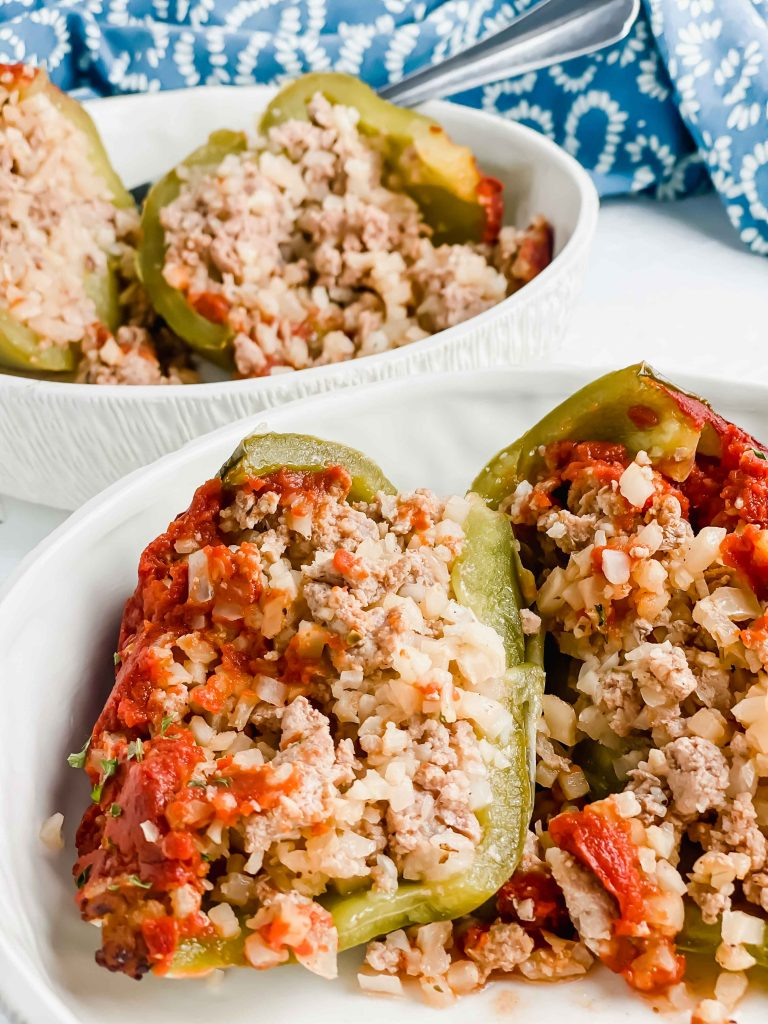 Image for Pork & Cauliflower Rice Stuffed Peppers of a cut open stuffed pepper in a white bowl. https://www.atwistedplate.com/pork-cauliflower-rice-stuffed-pepper/
