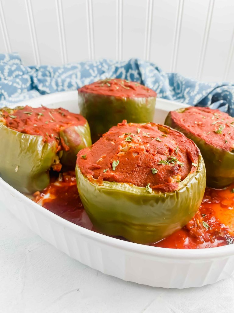 Image for Pork & Cauliflower Rice Stuffed Peppers of 4 stuffed green peppers in a white dish with a blue towel behind it. https://www.atwistedplate.com/pork-cauliflower-rice-stuffed-pepper/