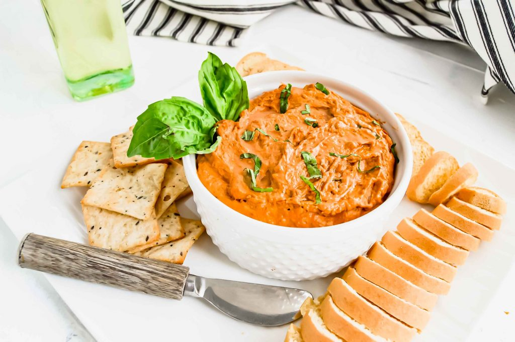 Dairy Free Sun-dried Tomato Dip in a white bowl, topped with basil on a square white plate with Gluten Free bread and crackers. There is a black and white towel and bottle of olive oil. https://www.atwistedplate.com/sun-dried-tomato-dip