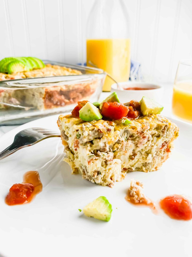 Easy Potato and Sausage Bake on a white plate topped with Avocado and Salsa with the casserole, bowl of salsa and Orange Juice against a white background. https://www.atwistedplate.com/easy-potato-and-sausage-bake/