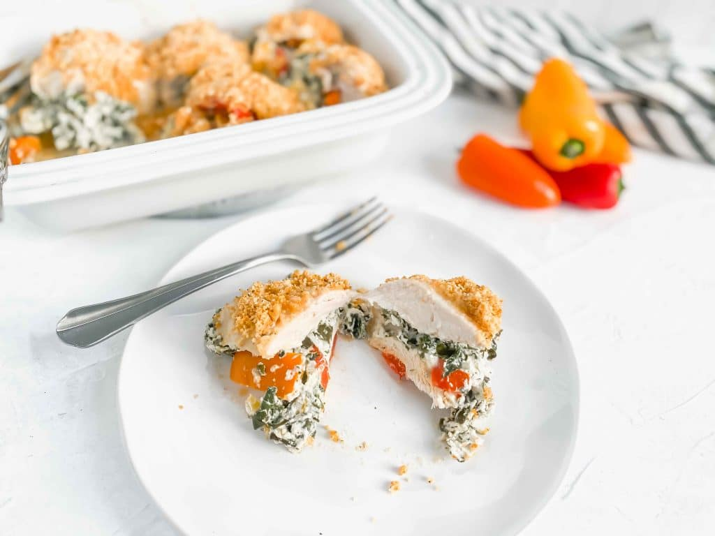 White dish with 5 stuffed chicken. There is bell peppers in the top right and a black/white towel under the dish. There is a plate with a cut stuffed chicken. https://www.atwistedplate.com/ricotta-&-spinach-chicken-with-pepper-and-almond-crumble/