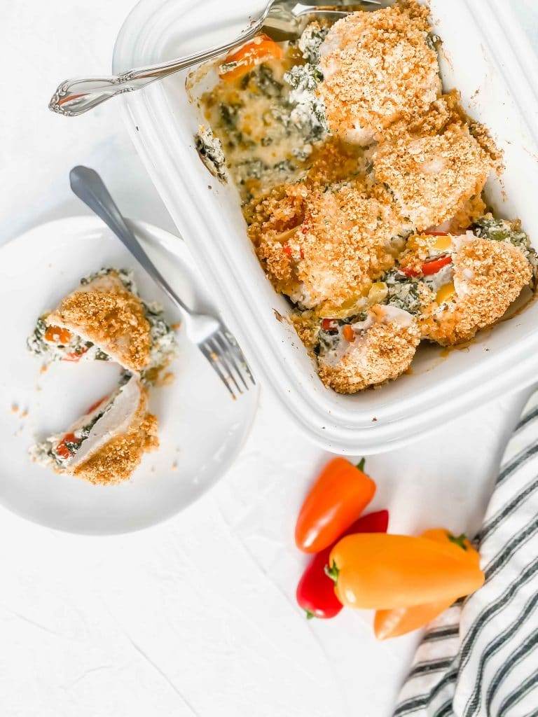 White dish with five Stuffed Chicken. There is bell peppers in the top right and a black/white towel under the dish. There is a plate with a cut stuffed chicken. https://www.atwistedplate.com/ricotta-&-spinach-chicken-with-pepper-and-almond-crumble/