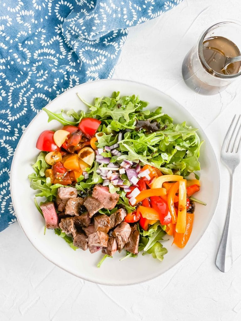 Steak and arugula salad in a white bowl with tomato, peppers red onion and basil balsamic dressing with a jar of dressing and a blue towel. https://www.atwistedplate.com/steak-arugula-salad/