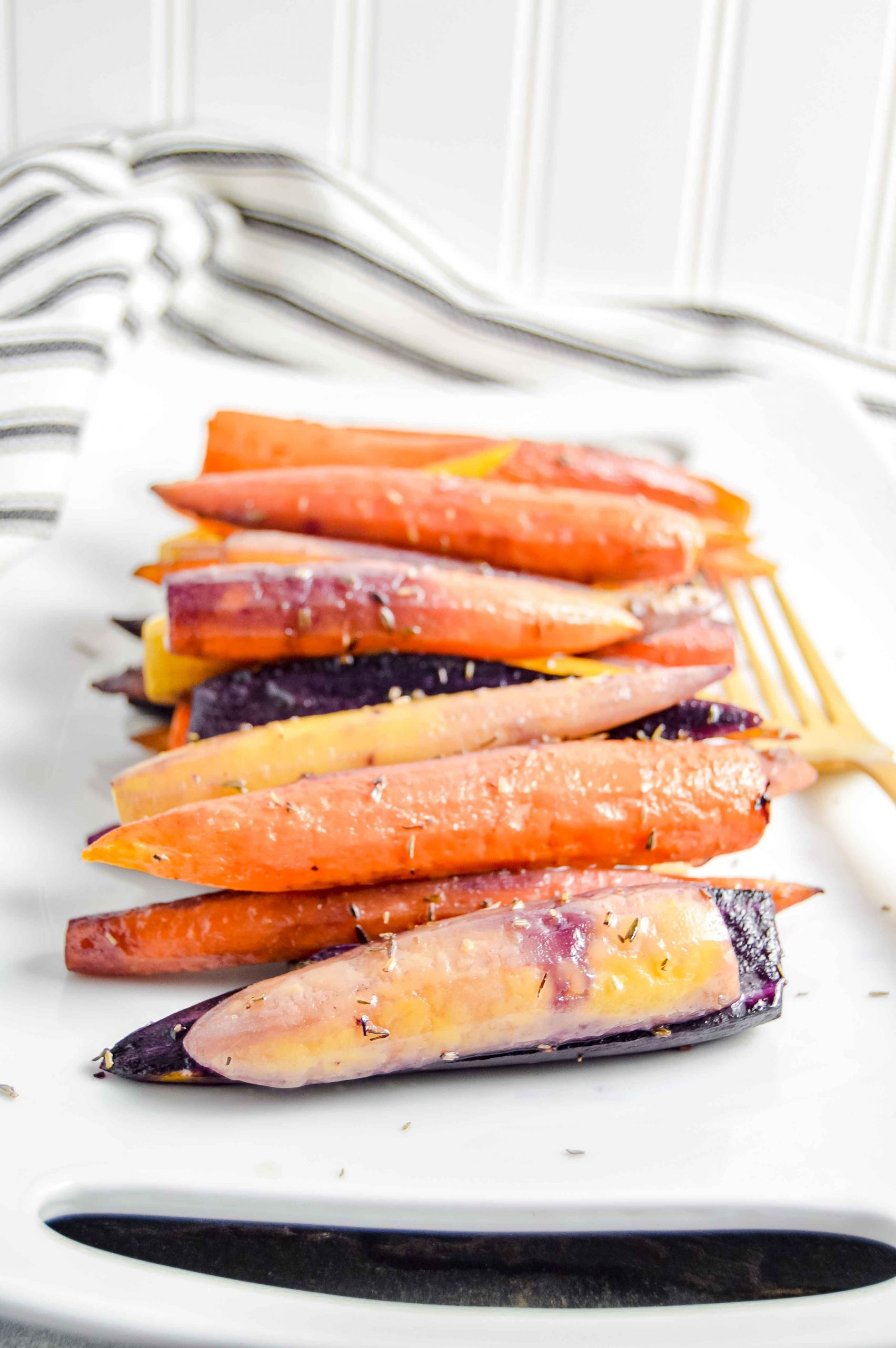Image of a side angle view of Perfectly Roasted Carrots on a rectangle white plate with a gold fork.  The plate sites on a gray blue background with a black and white striped towel in the top left corner.   https://www.atwistedplate.com/perfectly-roasted-carrots/
